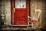 Photo of an old chair by a red door by Ryan Houston