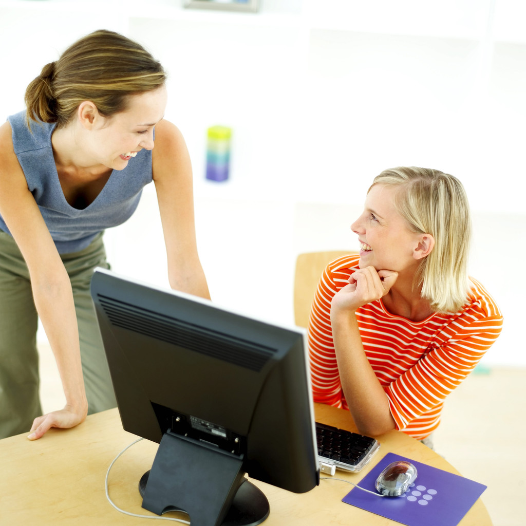 Two women sharing ideas in front of a computer