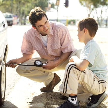 Father helping son fix a car
