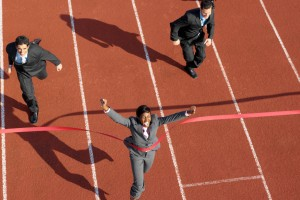Business woman crossing a track finish line